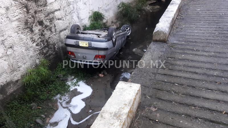 CONDUCTOR CAE CON VEHÍCULO EN ARROYO AL DERRAPAR EN CARRETERA NACIONAL EN SANTIAGO.